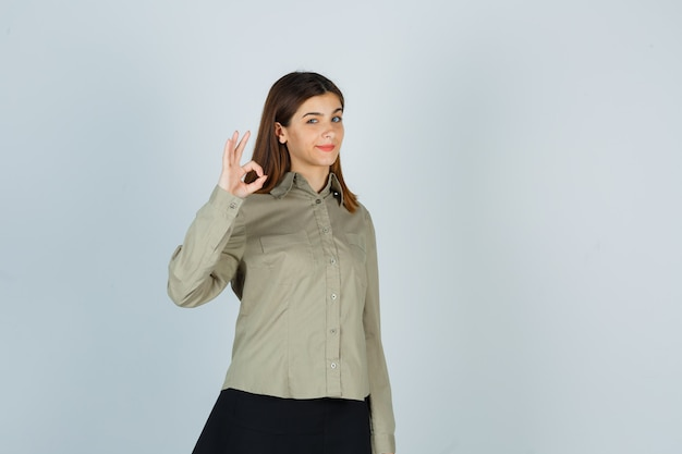 Giovane femmina che mostra gesto giusto in camicia, gonna e che sembra sicura Foto Gratuite