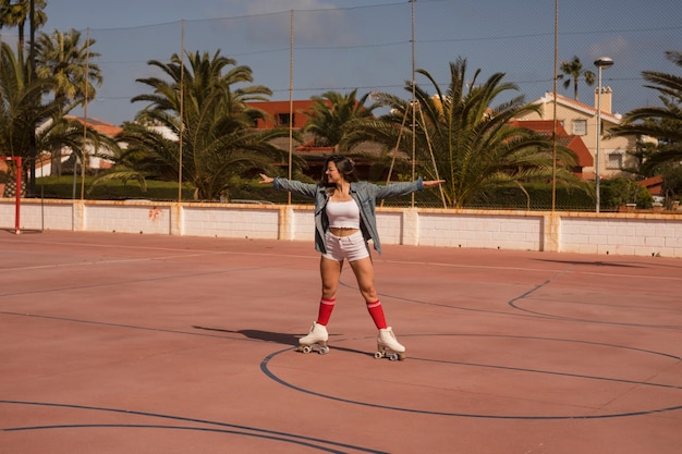 Young female skater exercising on an outdoor court Free Photo