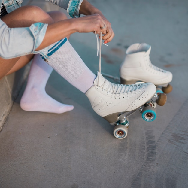 Young female skater tying the lace of roller skate Free Photo