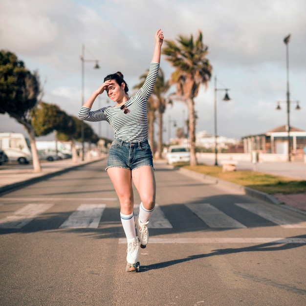 Young female skater with her arm raised dancing on road Free Photo