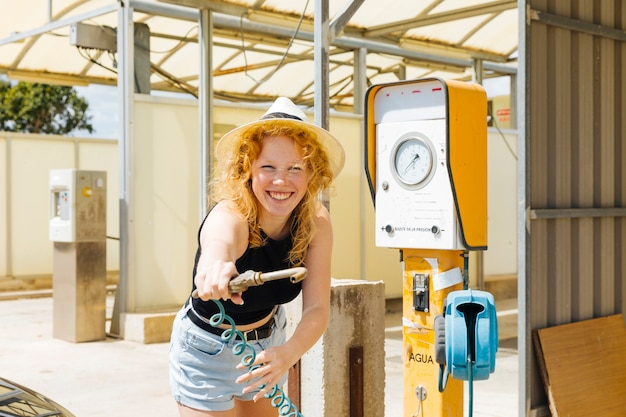Young female splashing with water tap at petrol station Free Photo