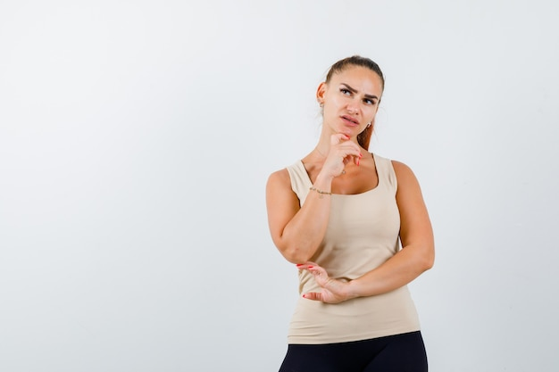 Young female standing in thinking pose in beige tank top and looking pensive , front view. Free Photo