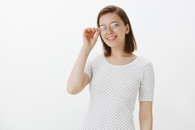 Молодая студентка выглядит довольной и уверенной в очках Бесплатные Фотографии