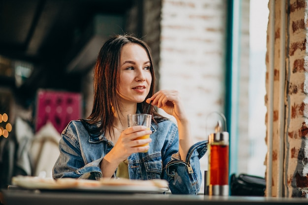 Young female student working on laptop in bar and eating pizza Free Photo