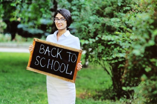 エレガントな服と看板を持っているメガネの若い女教師 Premium写真