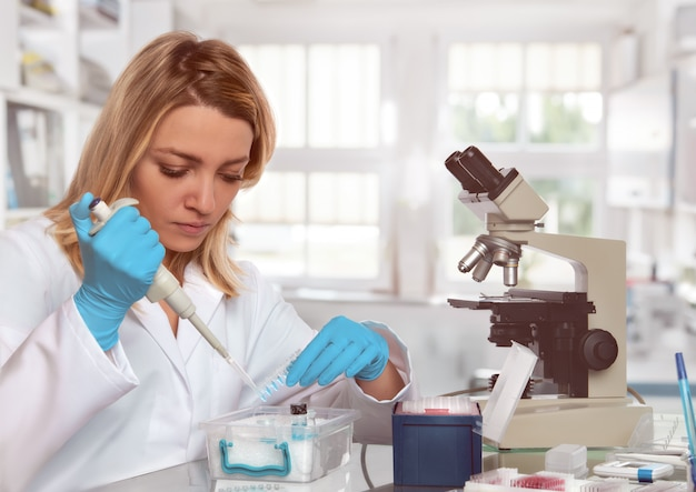 Young female tech or scientist loads liquid sample into test tubes Premium Photo