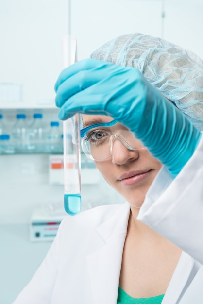 Young female tech or scientist with liquid sample into test tube Premium Photo