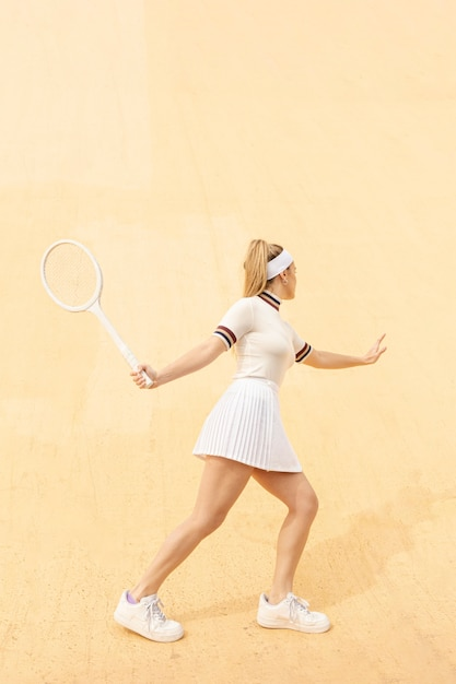Young female tennis player running after ball Free Photo