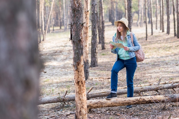 Young female traveler hiking in the forest holding map in hand Free Photo