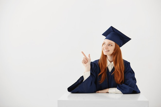 학문적 인 모자 가리키는 왼쪽 웃 고 테이블에 앉아 젊은 여성 대학 졸업. 아이디어를 보여주는 미래의 변호사 또는 엔지니어. 무료 사진