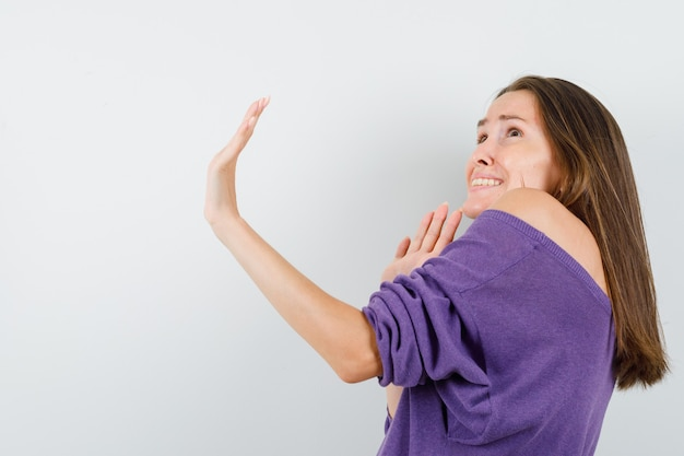 Young female in violet shirt showing stop gesture and looking scared . Free Photo