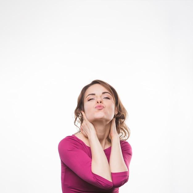 Giovane donna con apparenza accattivante morde le labbra sul fondale bianco Foto Gratuite