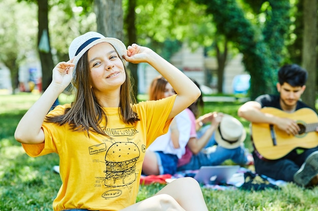 A young female with her friends having fun in park, sitting on the grass Free Photo