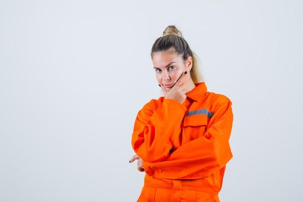 Giovane donna in uniforme da lavoro tenendo la mano sulla sua mascella mentre guarda lontano e guardando pensieroso, vista frontale. Foto Gratuite