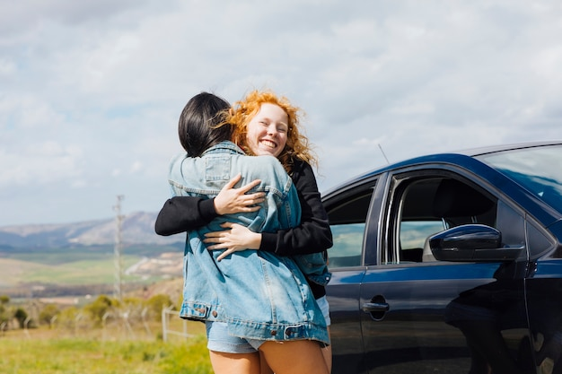 Young females hugging on roadside Free Photo