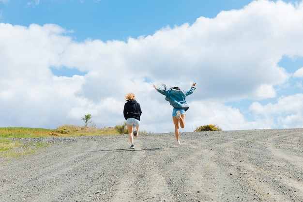 Young females jumping on empty road Free Photo