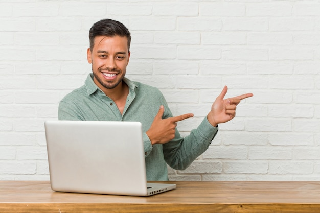 Young filipino man sitting working with his laptop excited pointing with forefingers away Premium Photo