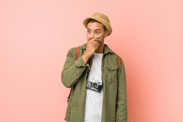 Young filipino traveler man thoughtful looking to a copycovering mouth with hand. Premium Photo