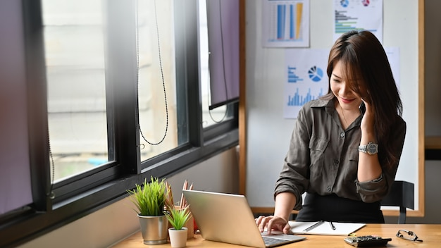 Young finance woman calling on phone and using laptop computer. Premium Photo