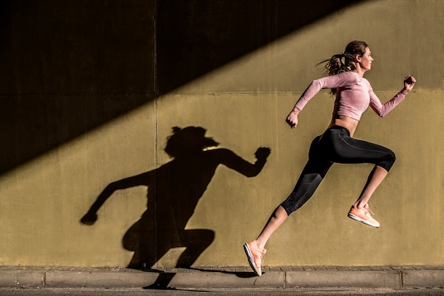 Young fit blonde woman jumping in the street Premium Photo