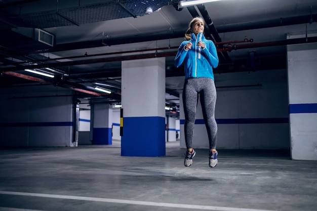 Young fit caucasian sportswoman in tracksuit running fast in garage. Premium Photo
