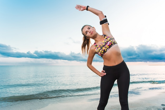 Young fit girl doing morning exercise on beach at sunrise Premium Photo
