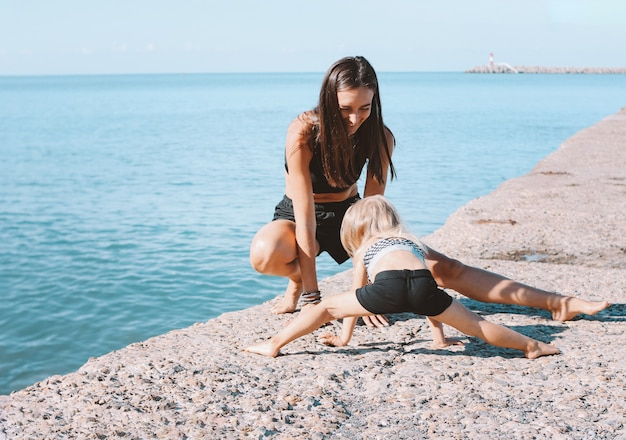 Young fit woman mom with little cute girl exercising on morning beach together Premium Photo