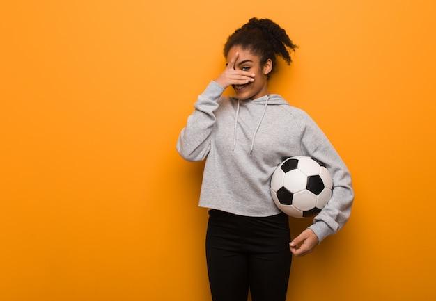 若いフィットネス黒人女性恥ずかしいと同時に笑っています。サッカーボールを保持しています。 Premium写真