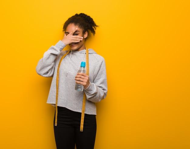 若いフィットネス黒人女性は恥ずかしいし、同じ時間を笑っています。水のボトルを保持しています。 Premium写真
