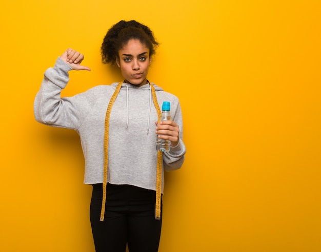 Young fitness black woman pointing fingers, example to follow.holding a water bottle. Premium Photo