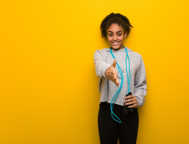 Young fitness black woman reaching out to greet someone. holding a jump rope. Premium Photo