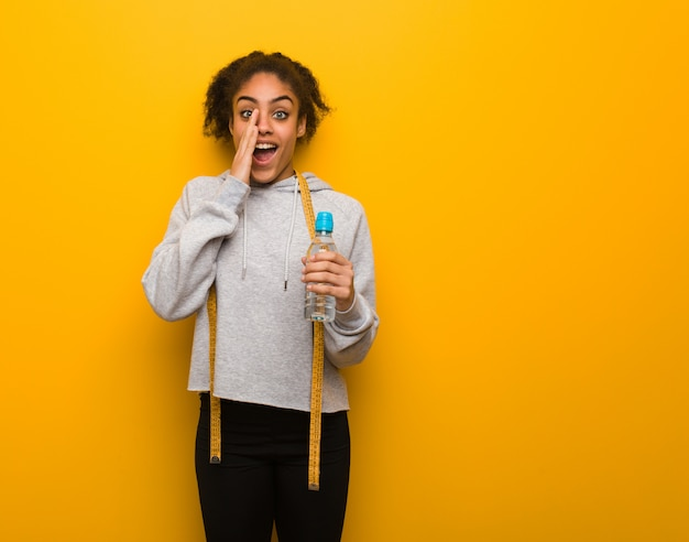 Young fitness black woman shouting something happy to the front.holding a water bottle. Premium Photo
