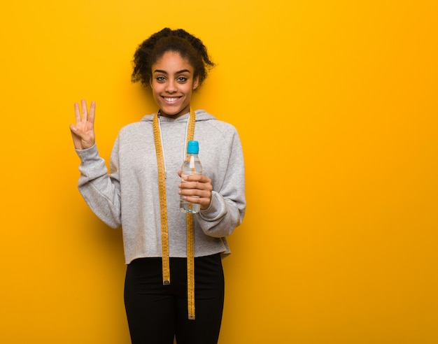 Young fitness black woman showing number three.holding a water bottle. Premium Photo