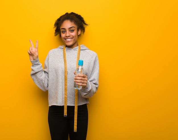 Young fitness black woman showing number two.holding a water bottle. Premium Photo