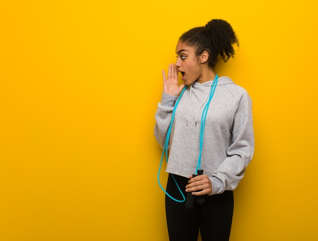 Young fitness black woman whispering gossip undertone. holding a jump rope. Premium Photo