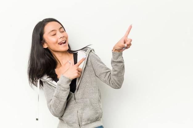 Молодая китаянка фитнеса указывая указательными пальцами на место для копирования, выражая волнение и желание. Premium Фотографии