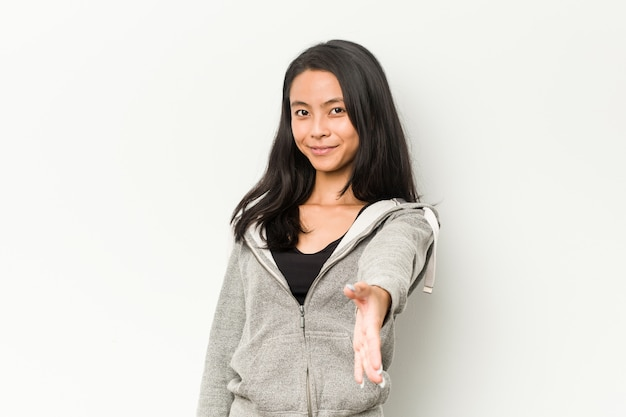 Young fitness chinese woman stretching hand at camera in greeting gesture. Premium Photo