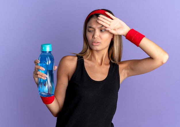 Giovane ragazza di forma fisica in abiti sportivi neri e fascia rossa che tiene una bottiglia d'acqua cercando stanco ed esausto dopo l'allenamento in piedi sopra la parete blu Foto Gratuite
