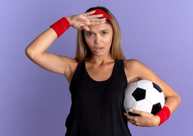 Giovane ragazza di forma fisica in abiti sportivi neri e fascia rossa che tiene pallone da calcio che guarda lontano con la mano sopra la testa sopra l'azzurro Foto Gratuite