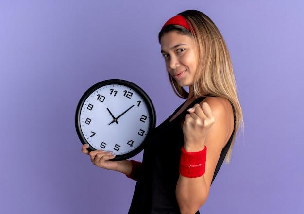 Giovane ragazza di forma fisica in abbigliamento sportivo nero e fascia rossa che tiene l'orologio da parete che stringe il pugno con la faccia seria che sta sopra la parete blu Foto Gratuite