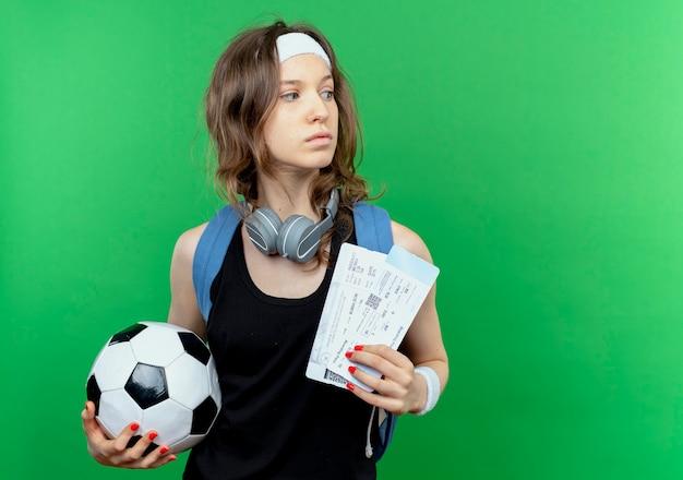 Giovane ragazza di forma fisica in abiti sportivi neri con zaino e fascia in possesso di pallone da calcio e biglietti aerei guardando da parte perplesso in piedi sopra la parete verde Foto Gratuite