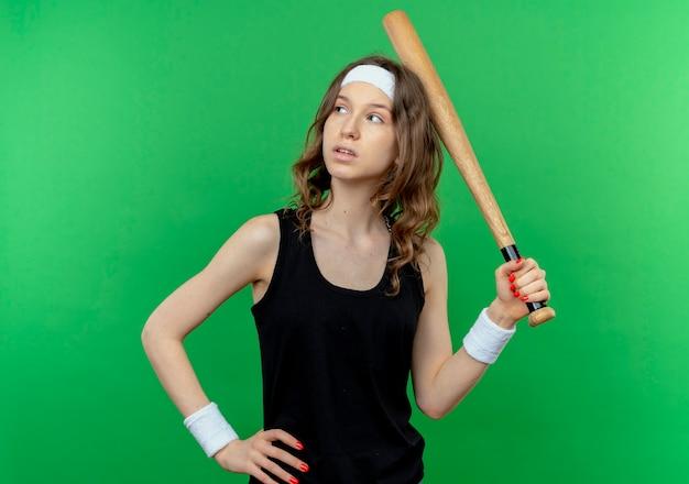 La giovane ragazza di forma fisica in abiti sportivi neri con la fascia che tiene la mazza di basaball sente la testa che osserva da parte con l'espressione pensierosa che sta sopra la parete verde Foto Gratuite