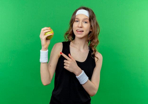 Giovane ragazza di forma fisica in abiti sportivi neri con la fascia che tiene la mela verde che indica con il dito sorridente che sta sopra la parete verde Foto Gratuite
