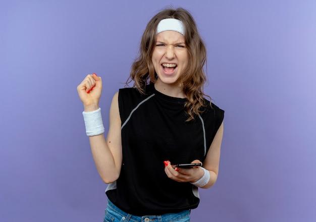 Giovane ragazza di forma fisica in abiti sportivi neri con fascia che tiene smartphone pugno di serraggio felice ed eccitato in piedi sopra la parete blu Foto Gratuite