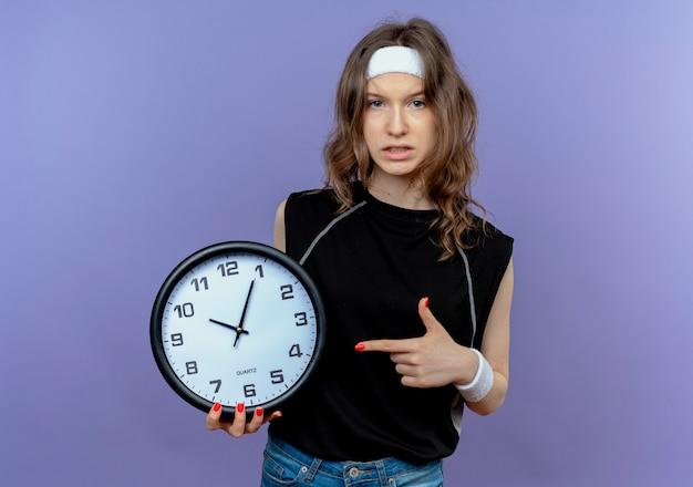 Giovane ragazza di forma fisica in abbigliamento sportivo nero con l'orologio di parete della tenuta della fascia che indica il dito con la faccia seria che sta sopra la parete blu Foto Gratuite