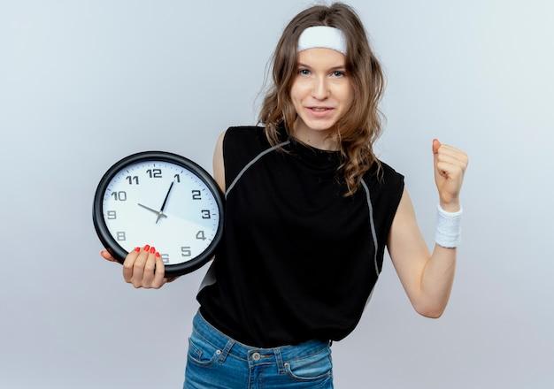 Giovane ragazza fitness in abiti sportivi neri con fascia tenendo l'orologio da parete sorridente fiducioso pugno di serraggio in piedi sul muro bianco Foto Gratuite