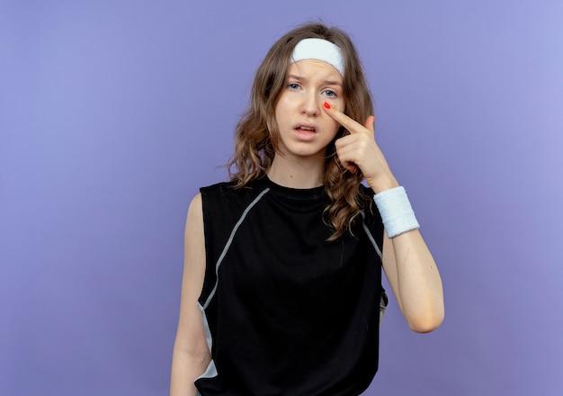 Giovane ragazza di forma fisica in abiti sportivi neri con archetto puntato con il dito al suo occhio in piedi sopra la parete blu Foto Gratuite