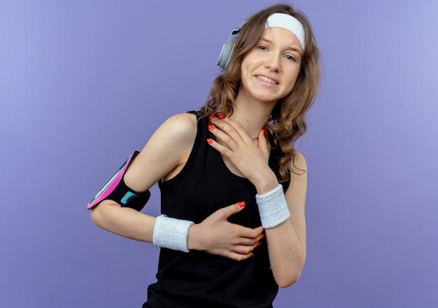 Giovane ragazza di forma fisica in abiti sportivi neri con fascia e fascia da braccio dello smartphone in piedi sopra la parete blu Foto Gratuite