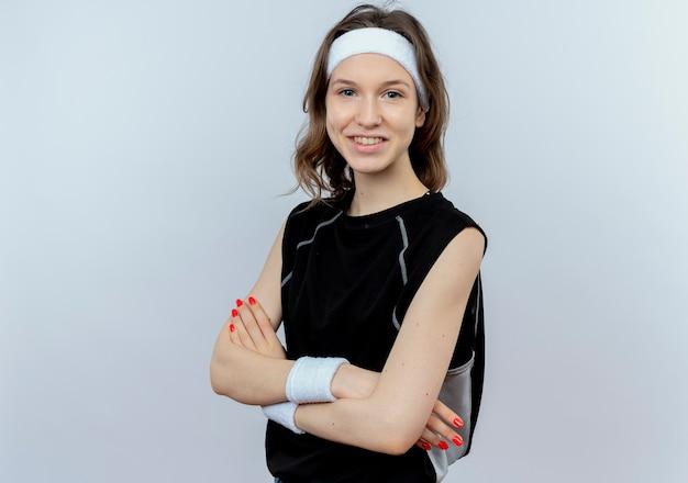 Giovane ragazza di forma fisica in abiti sportivi neri con fascia sorridente con le mani incrociate in piedi sopra il muro bianco Foto Gratuite