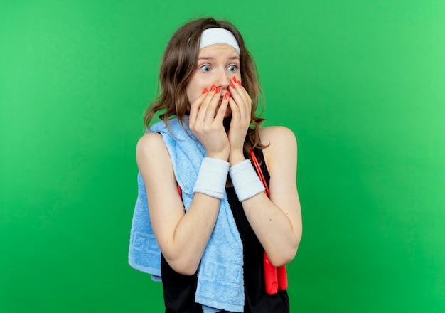 Giovane ragazza fitness in abiti sportivi neri con fascia e asciugamano sulla spalla che copre la bocca con le mani scioccate in piedi sopra la parete verde Foto Gratuite